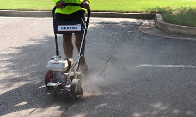 worker sealing crack in asphalt