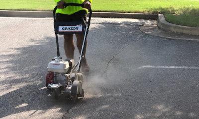 worker sealing crack in asphalt